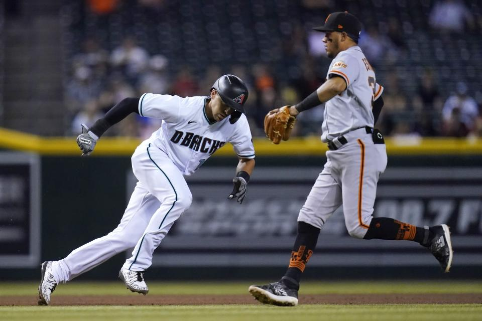 Arizona Diamondbacks' Nick Ahmed, left, runs past San Francisco Giants shortstop Thairo Estrada in a rundown between second and third during the fourth inning of a baseball game Tuesday, Aug. 3, 2021, in Phoenix. Ahmed was eventually tagged out. (AP Photo/Ross D. Franklin)