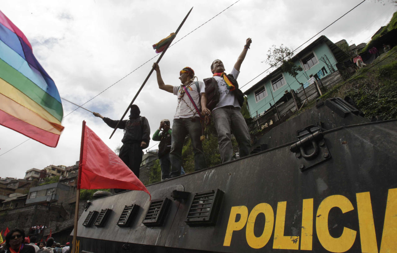 Protesters stand on a police vehicle during a march to protest President Rafael Correa's policies on mining in Quito, Ecuador, Thursday March 22, 2012. Protesters reached Ecuador's capital on Thursday after a two-week march from the Amazon to oppose plans for large-scaling mining projects on their lands. (AP Photo/Dolores Ochoa)