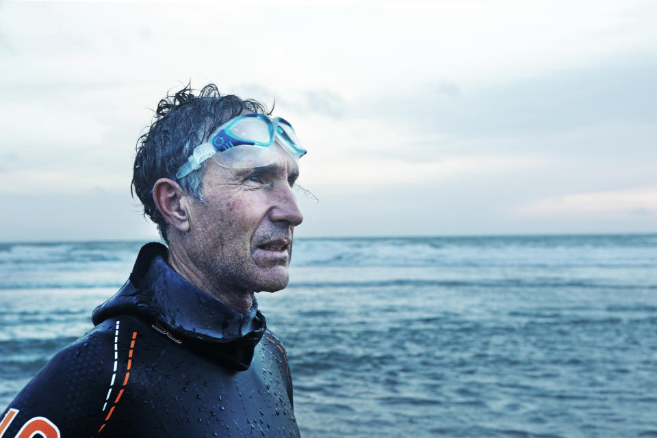 Older man stood on beach after swimming in the sea