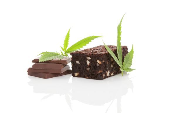 Cannabis leaves placed next to a brownie and pieces of chocolate.
