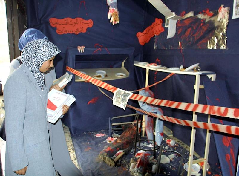 Palestinian students look at an exhibition at Al-Najah University in the West Bank town of Nablus 24 September 2001, commemorating the August 9 suicide bombing of the Sbarro pizzeria in Jerusalem which killed 15 people