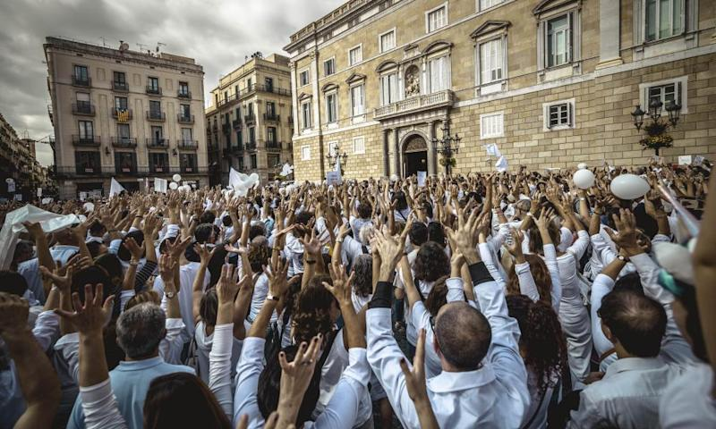 People raise their hands during a protest in favour of talks and dialogue in Sant Jaume square in Barcelona.