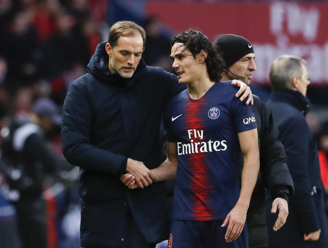 PSG coach Thomas Tuchel and PSG's Edinson Cavani speak during the French League One soccer match between Paris Saint-Germain and Bordeaux at the Parc des Princes stadium in Paris, Saturday, Feb. 9, 2019. (AP Photo/Christophe Ena)