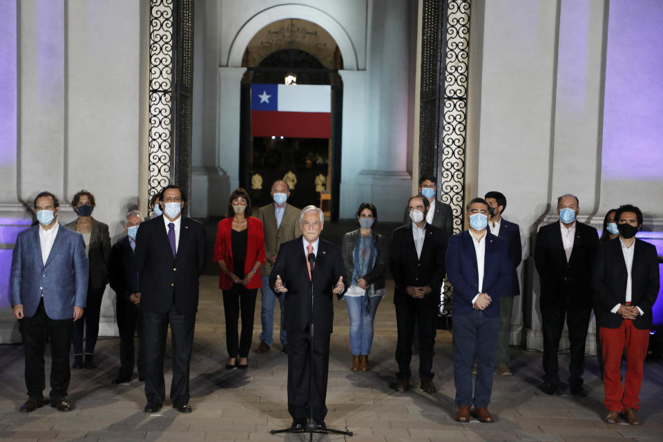 Chile's President Sebastian Pinera, center, speaks at La Moneda presidential palace on the day Chileans voted in a referendum to decide whether the country should replace its 40-year-old constitution, written during the dictatorship of Gen. Augusto Pinochet, in Santiago, Chile, Sunday, Oct. 25, 2020. (Dragomir Yankovic/Aton Chile via AP)