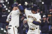 Milwaukee Brewers' Luis Urias is congratulated by Manny Pina (9) after hitting a two-run home run during the second inning of a baseball game against the Chicago Cubs Tuesday, April 13, 2021, in Milwaukee. (AP Photo/Morry Gash)