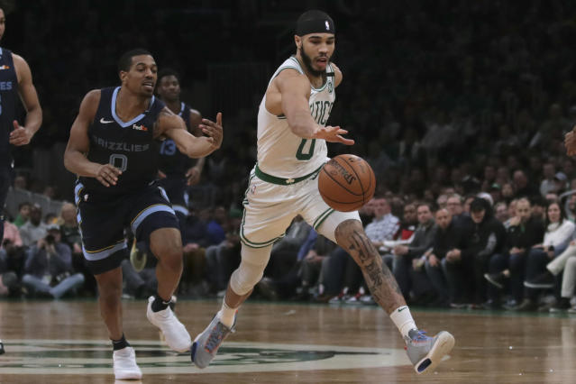Boston Celtics forward Jayson Tatum, right, chases a loose ball against Memphis Grizzlies guard De'Anthony Melton, left, during the second half of an NBA basketball game in Boston, Wednesday, Jan. 22, 2020. (AP Photo/Charles Krupa)