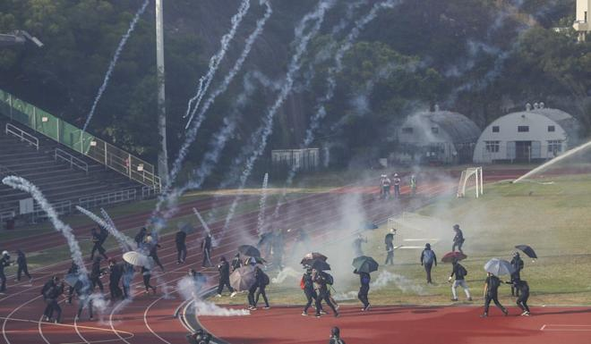 Clashes erupt between anti-government protesters and riot police in a sports field at Chinese University. Photo: Winson Wong