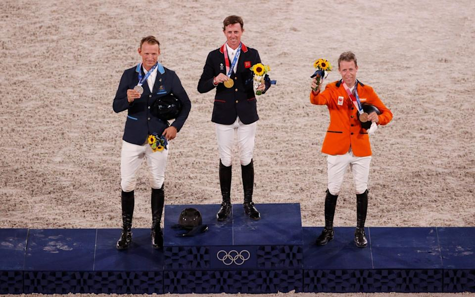 Ben Maher poses with his gold medal on the podium - GETTY IMAGES