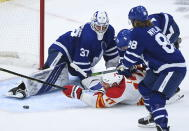 Toronto Maple Leafs goaltender Michael Hutchinson (30) makes a save against Calgary Flames left wing Milan Lucic (17) as Maple Leafs center Travis Boyd (72) gets a penalty on the play while Maple Leafs right wing William Nylander (88) looks on during the second period of an NHL hockey game in Toronto on Monday, Feb. 22, 2021. (Nathan Denette/The Canadian Press via AP)