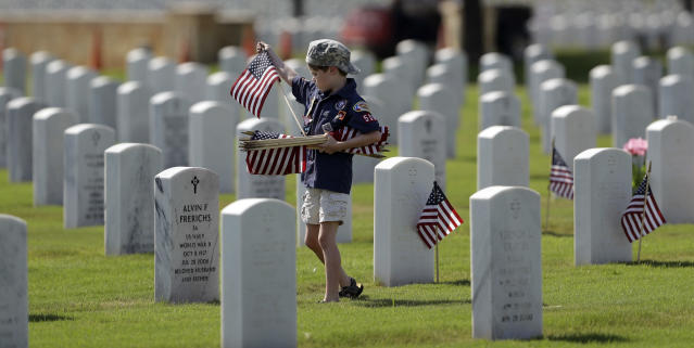 <p>A Boy Scout helps place some of the more than 100,000 U.S. flags next to headstones at Fort Sam Houston National Cemetery in preparation of Memorial Day, Friday, May 25, 2018, in San Antonio. Texas. (Photo: Eric Gay/AP) </p>