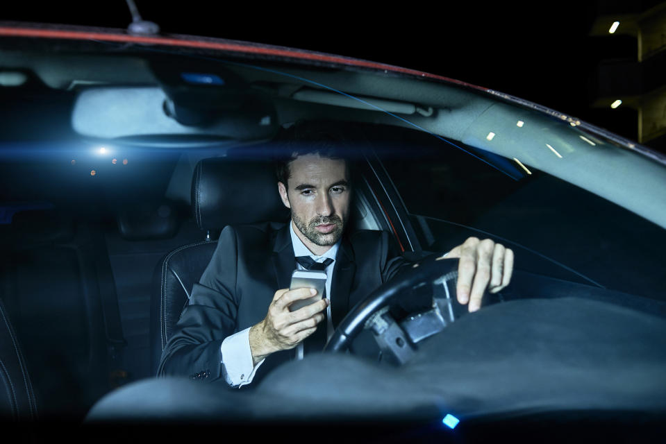 A file picture of a man in a suit using his mobile phone in his car.
