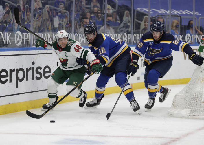 Minnesota Wild's Jared Spurgeon (46) battles St. Louis Blues' Zach Sanford (12) and Mackenzie MacEachern (28) for the loose puck in the second period of an NHL hockey game, Wednesday, May 12, 2021 in St. Louis. (AP Photo/Tom Gannam)