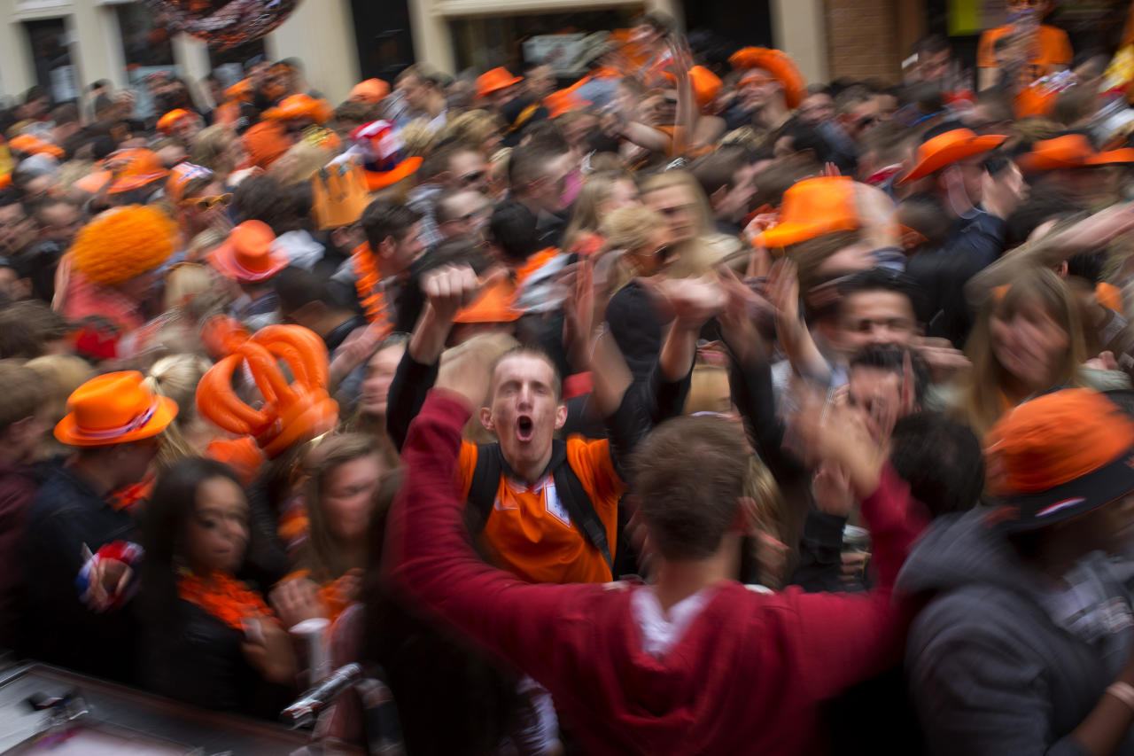 People dance on the street in Amsterdam, The Netherlands, Tuesday April 30, 2013. Around a million people are expected to descend on the Dutch capital for a huge street party to celebrate the first new Dutch monarch in 33 years. (AP Photo/Emilio Morenatti)