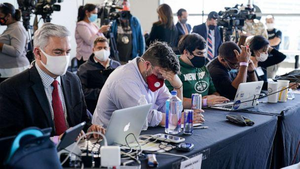 PHOTO: Election observers sit in front of the media as vote counting in the general election continues at State Farm Arena on Thursday, Nov. 5, 2020, in Atlanta. (Brynn Anderson/AP)
