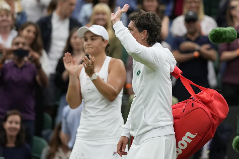 Spain's Carla Suarez Navarro leaves the court after being defeated by Australia's Ashleigh Barty, left, in the women's singles first round match against on day two of the Wimbledon Tennis Championships in London, Tuesday June 29, 2021. (AP Photo/Kirsty Wigglesworth)