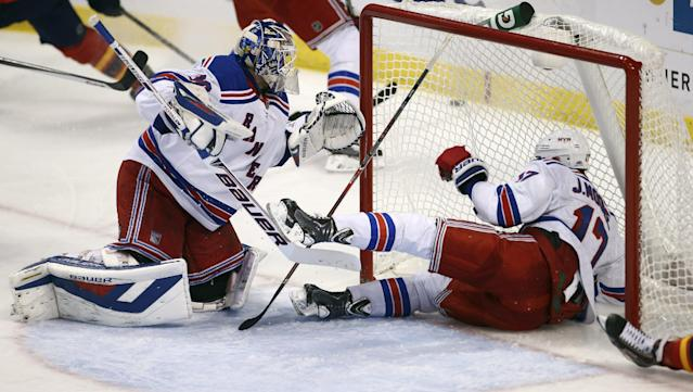 New York Rangers' John Moore (17) slides past goalie Henrik Lundqvist (3) into the goal as they try to stop a Florida Panthers' shot during the second period of an NHL hockey game in Sunrise, Fla., Wednesday, Nov. 27, 2013. (AP Photo/J Pat Carter)
