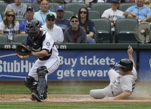 New York Yankees' Mark Teixeira, right, scores ahead of the throw to Seattle Mariners catcher Brandon Bantz in the first inning of a baseball game on Saturday, June 8, 2013, in Seattle. (AP Photo/Ted S. Warren)
