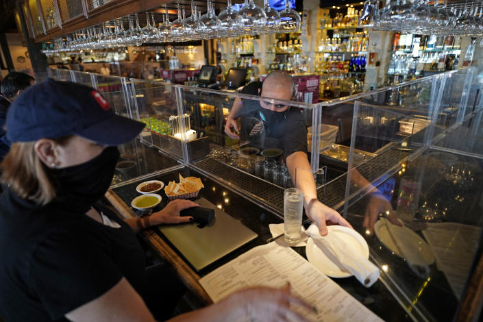 Bartender Daniel Vazquez, right, paces a plate to Betsy Campbell as she eats lunch at Picos Mexican restaurant Wednesday, March 10, 2021, in Houston. Picos, like many restaurants across the state, continue to operate at a reduced capacity and ask customers to wear masks despite Texas Gov. Greg Abbott ending state mandates for COVID-19 safety measures Wednesday. (AP Photo/David J. Phillip)