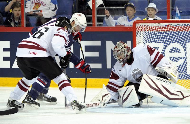 USA's David Moss, center, scores against Latvia's Krisjanis Redhils and goalie Edgars Masalskis during the 2013 Ice Hockey IIHF World Championships Group B match Latvia vs USA in Helsinki, Finland, on Sunday May 5, 2013. (AP Photo / LEHTIKUVA, Jussi Nukari) FINLAND OUT - NO SALES