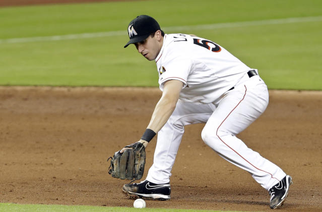 Miami Marlins third baseman Ed Lucas drops the ball for an error as Atlanta Braves' Elliot Johnson is safe at first in the sixth inning during a baseball game, Tuesday, Sept. 10, 2013 in Miami. (AP Photo/Lynne Sladky)