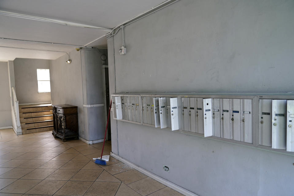 Open mailboxes are shown in an empty lobby at the Devon apartment building, Wednesday, July 14, 2021, in Miami Beach, Fla. Residents of the 82-year-old building were ordered to evacuate this week because of concrete deterioration. The building is several miles from Surfside, where the Champlain Towers South collapsed almost three weeks ago. (AP Photo/Lynne Sladky)