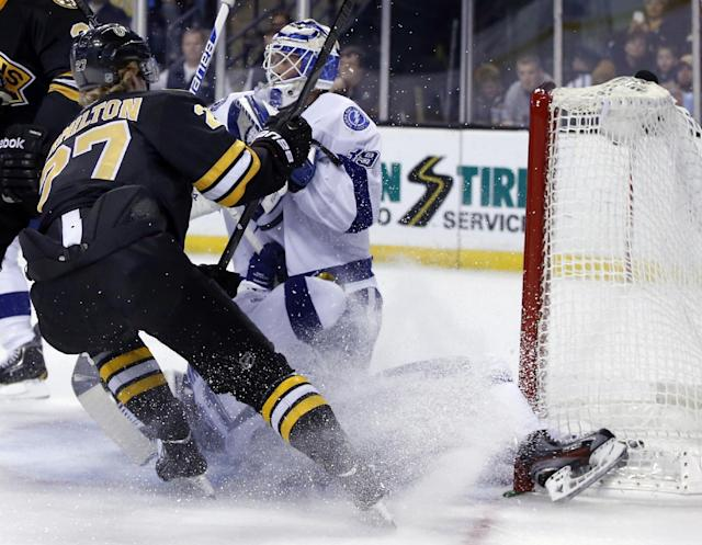 Tampa Bay Lightning center Steven Stamkos, below, bangs into the goalpost defending against Boston Bruins defenseman Dougie Hamilton (27) as goalie Anders Lindback defends the net during the second period of an NHL hockey game in Boston Monday, Nov. 11, 2013. Stamkos was taken off the ice on a stretcher after the play. (AP Photo/Elise Amendola)