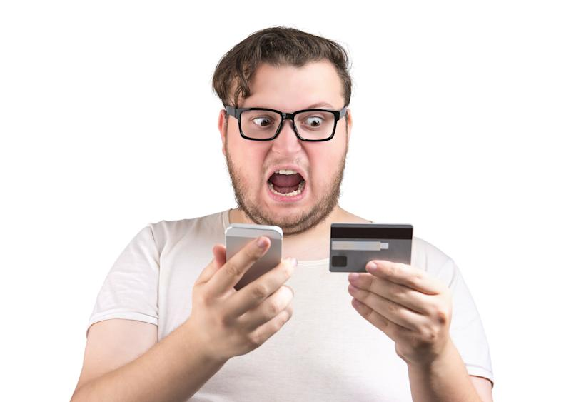 Man in glasses holding credit card and using smartphone while screaming because of lost and mistake