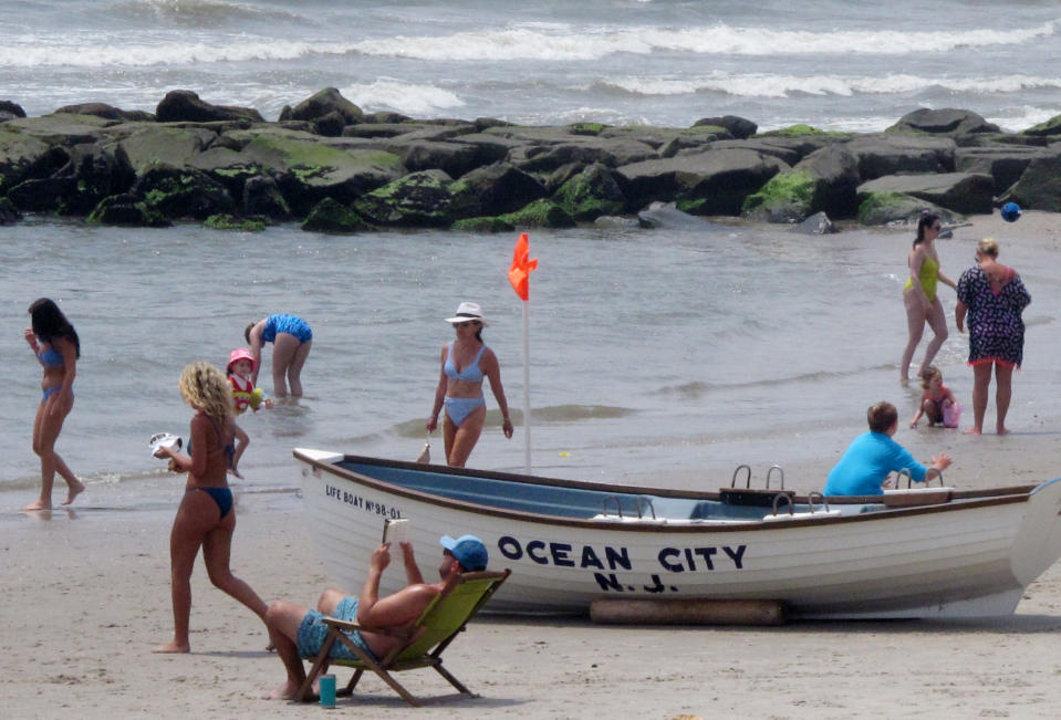 This July 8, 2021 photo shows beachgoers on the sand in Ocean City, N.J. Numerous residents of Ocean City are among those who oppose three offshore wind farms planned for the ocean off their city, fearing their impact on the ocean, the environment and the economy. (AP Photo/Wayne Parry)