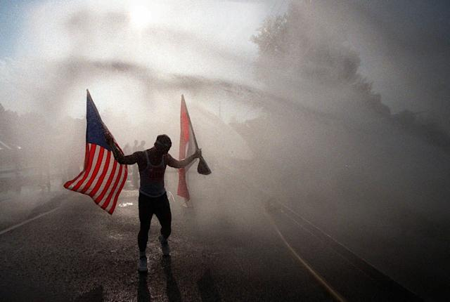 <p>Nyoman Budiartha of Decatur, Ga., holds an American flag and an Indonesian flag as his cools off in a water spray after running the Peachtree Road Race in Atlanta, Ga., Saturday, morning, July 4, 1998. (Photo: John Bazemore/AP) </p>