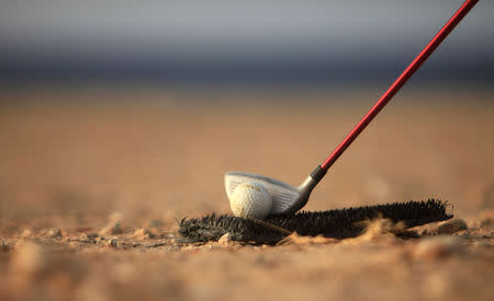 FILE PHOTO: A golf club is positioned near a ball as a boy plays a game near the beach in Gargaresh area in Tripoli