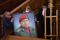 First Lady Cilia Flores, center, and Socialist party leader Diosdado Cabello, left, carry a portrait of late Venezuelan President Hugo Chavez into the chamber of the National Assembly as the ruling socialist party prepares to assume the leadership of Congress in Caracas, Venezuela, Tuesday, Jan. 5, 2021. Ruling party allies swept legislative elections last month boycotted by the opposition. (AP Photo/Matias Delacroix)