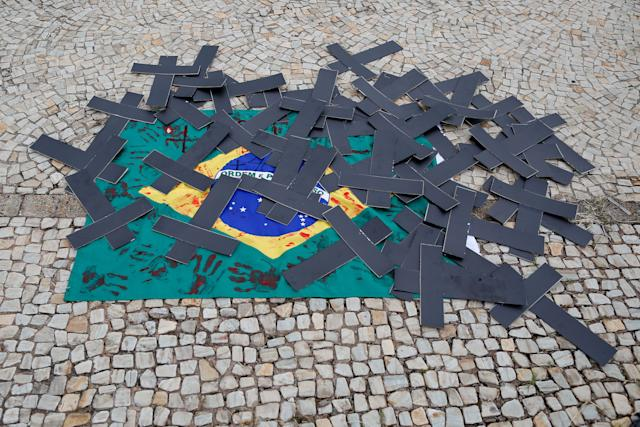 Black crosses and a Brazilian flag tainted with red ink are seen during a demonstration by nurses to protest against Brazilian President Jair Bolsonaro and pay tribute to health workers who died from complications of the novel coronavirus COVID-19, in front of Planalto Palace in Brasilia, on May 1, 2021. - Brazil is the most populous population American population affected by the pandemic, with more than 403,781 deaths and 14,659. 011 infections so far. (Photo by Sergio LIMA / AFP) (Photo by SERGIO LIMA/AFP via Getty Images)