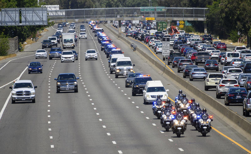 A funeral hearst is led by an honor procession for Sacramento police officer Tara O'Sullivan as they drives along Highway 99 on the outskirts of Sacramento, on its way to the funeral home in Elk Grove, Calif. on Friday, June 21, 2019. O'Sullivan, 26, and other officers were helping a woman gather her belongings from a Sacramento home as part of a domestic violence call when the shooting occurred Wednesday evening. (Paul Kitagaki Jr./The Sacramento Bee via AP)