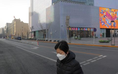 A Chinese woman wears a mask as she walks in an empty street after Chinese New Year celebrations were cancelled in Beijing, - Credit: Rex