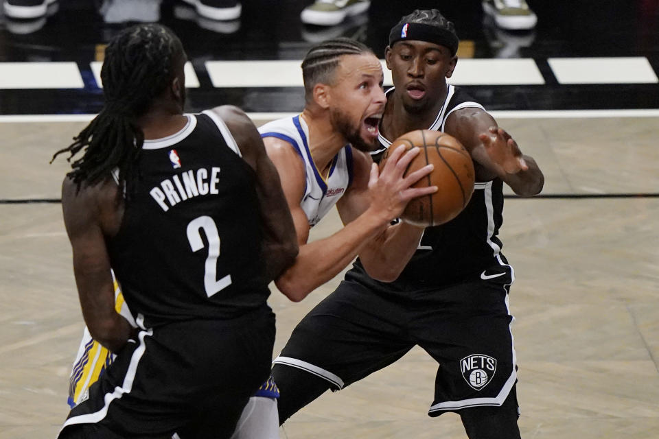Brooklyn Nets forward Taurean Prince (2) and Brooklyn Nets guard Caris LeVert (22) defend Golden State Warriors guard Stephen Curry (30) as Curry looks to shoot during the first quarter of an opening night NBA basketball game, Tuesday, Dec. 22, 2020, in New York. (AP Photo/Kathy Willens)
