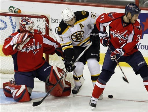 Washington Capitals center Brooks Laich (21) and Boston Bruins center Patrice Bergeron (37) lose track of the puck as Capitals goalie Tomas Vokoun, left, of the Czech Republic, covers the net during the first period of an NHL hockey game in Washington, Sunday, Feb. 5, 2012. (AP Photo/Ann Heisenfelt)