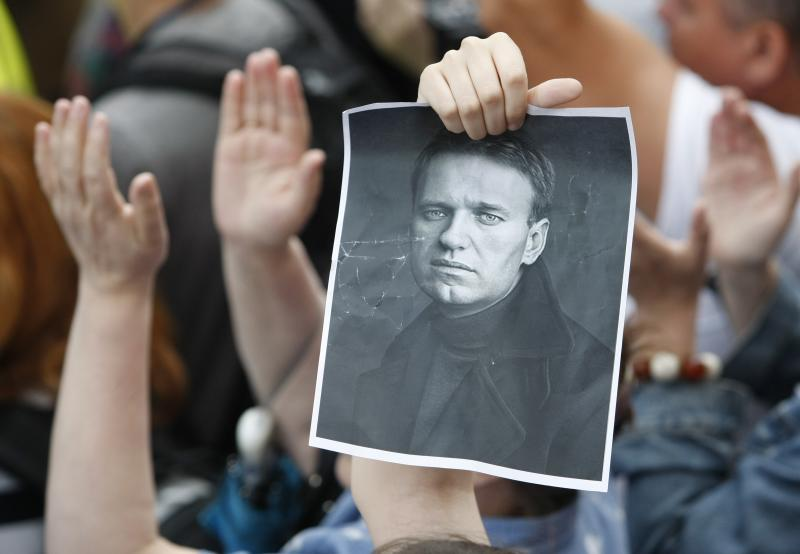 People hold a poster of opposition figure Alexei Navalny , as they gather in support of him in Moscow, Russia, Thursday, July 18, 2013. Navalny was convicted of embezzlement Thursday and sentenced to five years in prison, a harsh ruling his supporters called an obvious attempt to shut down a top foe of President Vladimir Putin and intimidate other opposition activists. (AP Photo/Denis Tyrin)