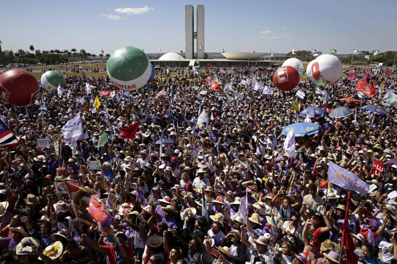 Women participate in the Margaridas march, in front of the Brazilian National Congress, in Brasilia, Brazil, Wednesday, Aug. 14, 2019. The Margaridas, or Daisies, formed to honor Margarida Maria Alves, a murdered local leader of the Rural Worker's Union, renowned for surmounting the embedded cultural stereotypes and obstacles for women, especially those working in rural areas. (AP Photo/Eraldo Peres)