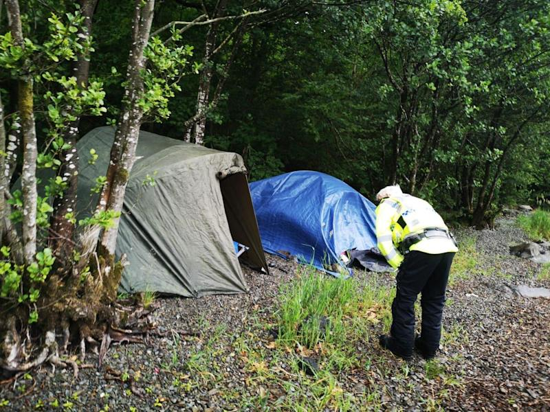 An officer speaks to people illegally camping in the Lake District. Overnight stays are not yet allowed until coronavirus lockdown measures ease further on 4 July: Tony Watson