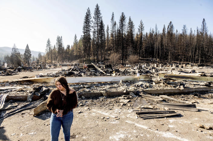 Kyra Cedillos, 14, stands in front of the remains of Hunter Ace Hardware, destroyed by the Dixie Fire, in the Greenville community of Plumas County, Calif., on Sunday, Sept. 5, 2021. Cedillos was helping grandmother Kimberly Price feed cats left behind by Dixie Fire evacuees. (AP Photo/Noah Berger)