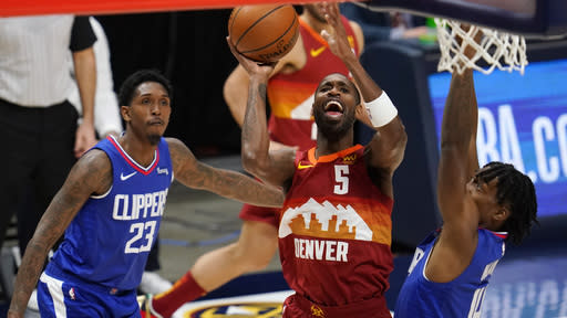 Denver Nuggets forward Will Barton, center, drives to the basket between Los Angeles Clippers guards Lou Williams, left, and Terance Mann during the first half of an NBA basketball game Friday, Dec. 25, 2020, in Denver. (AP Photo/David Zalubowski)