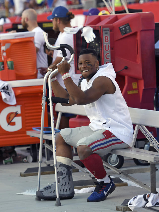 New York Giants running back Saquon Barkley smiles as he sits on the bench during the second half of an NFL football game against the Tampa Bay Buccaneers Sunday, Sept. 22, 2019, in Tampa, Fla. Barkley was injured in the first half. (AP Photo/Jason Behnken)