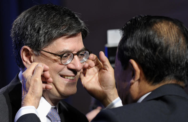 Japanese Finance Minister Taro Aso, right, rubs the cheeks of Treasury Secretary Jacob Lew before they gathered for a photo with the Group of 20, Friday, Oct. 11, 2013, at the International Monetary Fund (IMF) headquarters in Washington. Finance ministers and central bank officials from the Group of 20 nations are in Washington ahead of weekend meetings of the 188-nation International Monetary Fund and its sister lending organization, the World Bank. (AP Photo/Susan Walsh)