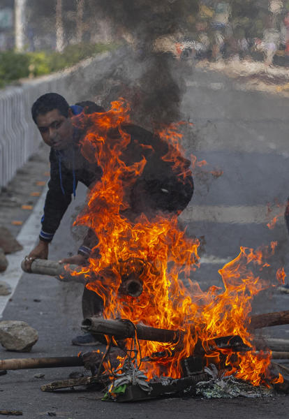 A protestor sets fire to block traffic in Gauhati, India, Thursday, Dec. 12, 2019. Police arrested dozens of people and enforced curfew on Thursday in several districts in India's northeastern Assam state where thousands protested legislation granting citizenship to non-Muslims who migrated from neighboring countries. (AP Photo/Anupam Nath)