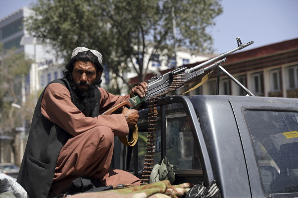A Taliban fighter sits on the back of a vehicle with a machine gun in front of the main gate leading to the Afghan presidential palace, in Kabul, Afghanistan, Monday, Aug. 16, 2021. (Rahmat Gul/AP Photo)