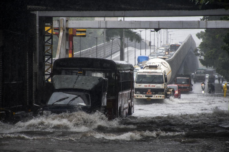 Vehicles drive through Waterlogged road due to heavy rain at Gandhi Market, Sion, on July 15, 2020 in Mumbai, India. (Photo by Pratik Chorge/Hindustan Times via Getty Images)