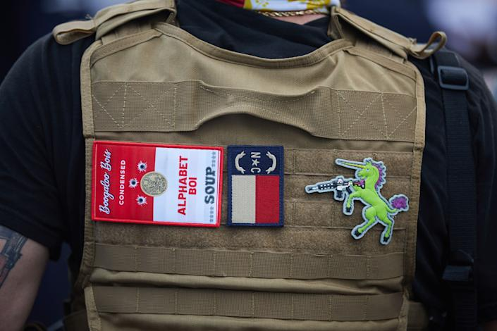 A member of the far-right militia, Boogaloo Bois, walks next to protestors demonstrating outside Charlotte Mecklenburg Police Department Metro Division 2 just outside of downtown Charlotte, North Carolina, on May 29, 2020. (Logan Cyrus/AFP via Getty Images)