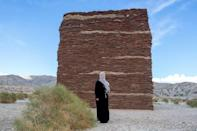 "Saudi artist Zahrah Al Ghamdi stands by her piece ""What Lies Behind the Walls"" at the Desert X exhibit"