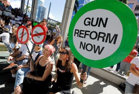 FILE PHOTO: Protesters hold signs as they call for a reform of gun laws three days after the shooting at Marjory Stoneman Douglas High School, at a rally in Fort Lauderdale, Florida, U.S., February 17, 2018. REUTERS/Jonathan Drake/File Photo