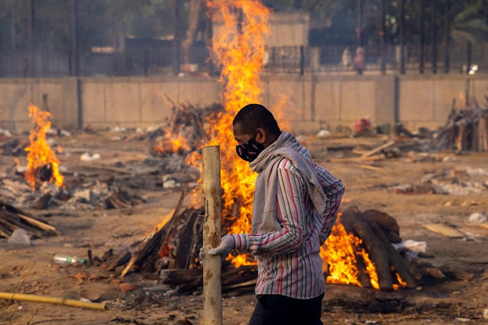 A man walks past burning funeral pyres of people, who died due to the coronavirus disease (COVID-19), at a crematorium ground in New Delhi, India, April 22, 2021. REUTERS/Danish Siddiqui     TPX IMAGES OF THE DAY (Photo: DANISH SIDDIQUI via REUTERS)